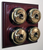 Quadruple Mahogany Pattress with Plain Brass Black Ceramic Dolly Switches