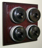 Quadruple Mahogany Pattress with Plain Antique Brass Ivory Ceramic Dolly Switches