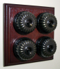 Quadruple Mahogany Pattress with Ribbed Antique Brass Black Ceramic Dolly Switches
